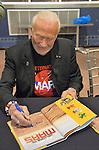 Garden City, New York, USA. October 23, 2015. Former NASA astronaut Edwin BUZZ ALDRIN autographs his new book Welcome to Mars: Making a Home on the Red Planet, a National Geographic Kids book for Middle Grades. Before that, Aldrin discussed his childhood, experiences in space, and importance of  exploring Mars, in the jetBlue Sky Theater Planetarium at Long Island's Cradle of Aviation Museum.  Aldrin is wearing his Destination MARS shirt. On the 1969 Apollo 11 mission, Aldrin was the second person ever to walk on the Moon, and his first trip to space was the1966 Gemini 12.