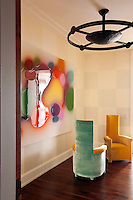 An artwork by Peter Zimmermann glows on the wall of the landing which is furnished with a pair of armchairs by Jean-Paul Phelippeau and a pendant light by Philippe Anthonioz