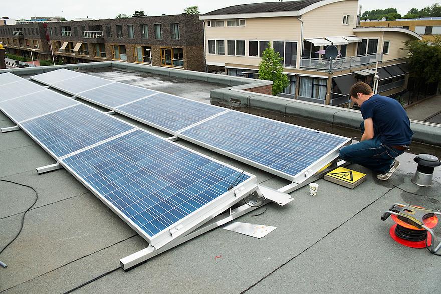 Nederland, Utrecht, 17 juni  2013<br /> Montage van zonnepanelen op het dak van een school<br /> Foto(c): Michiel Wijnbergh