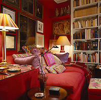 The walls of the small Red Library are clad in scarlet hand-woven silk moire and the red sofa is covered with needlepoint cushions