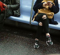 A teenager on the subway in New York texts while wearing her fashionably ripped jeans, seen on Sunday, February 28, 2016. (© Richard B. Levine)