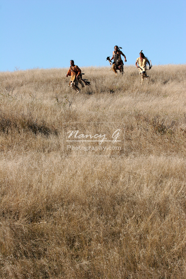 Three Native American Indian men running in the dead grasses