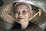 An elderly oriental woman smiles from under her hat.