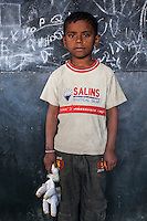 Krishu, 5, poses for a portrait with a soft toy in the Guria Non-Formal Education center in the middle of the Shivdaspur red light district, Varanasi, Uttar Pradesh, India on 20 November 2013. Guria uses the soft toys as a form of therapy for the children of the women in prostitution and also use it as signals of the children's emotional wellbeing.