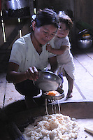 Mother prepares traditional 'Chicas' in jungle home with child at side. Every indigenous women has her signature 'Chicas' Its an alcoholic drink prepared from the yucca plant fermented with her personal saliva (spit).