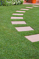 Stepping stones in perfect lawn grass, leading in an arc to backyard patio, with perennial plants and flowers at rear