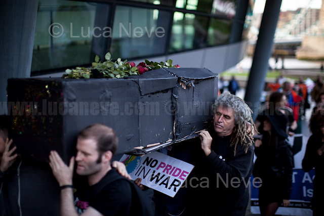 London, 24/05/2016. Today, LGBTQUI (Lesbian, Gay, Bisexual, Transgender, Queer or Questioning, and Intersex) and antimilitarist groups - including Veterans for Peace - held a demonstration and a vigil outside City Hall to protest against the RAF's Red Arrows fly over the Pride in London Parade 2016. From the organisers Facebook page: &lt;&lt;[&hellip;] We represent a cross-section of people from the LGBTQ community and anti-militarist groups who were shocked and outraged by the announcement that the Red Arrows would be flying over London Pride this year. The British military is deeply implicated in a history of homophobic and transphobic oppression, and is responsible for the destruction of human lives, including those of foreign LGBTQ communities, and the social infrastructure that supports them. On a day that commemorates and celebrates the courageous struggles of past and present LGBTQ individuals and communities against oppression and violent prejudice, we find it deeply offensive that the event is providing a platform for the RAF to sanitise its image and divert attention away from its role in executing British military objectives across the world, and the human suffering that such operations involve. We demand the unreserved withdrawal of the invitation of BAE Systems to march on this year&rsquo;s parade, and of the RAF's Red Arrows (which includes BAE-provided aircrafts) to fly over the parade. We call upon all concerned individuals and groups from within and without the LGBTQ community to join us in protesting this attempt to use London Pride as a branding exercise and divert attention away from complicity in war crimes and needless human suffering. Because we take Pride in radically challenging gendered and sexual oppression, not in assimilation to the status quo. Because an injustice to one is an injustice to all. Because there is No Pride in War. [&hellip;]&gt;&gt;.<br /> <br /> For more information please click here: https://neveragainever.org/ &amp; htt