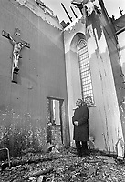 Roman Catholic Bishop of Down and Connor, Dr Patrick Walsh, stands inside the burnt-out remains of the Church of the Virgin Mary and Saint Brigid, Magheranesk, near Glenavy, Co Antrim, N Ireland, UK, burnt in a secterian attack, November 1991. 199111234. <br /> Copyright Image from Brendan Murphy, c/o Irish News, 113 Donegall Street, Belfast, UK, BT1 2GE...Tel: +44 28 9032 2226.Email: photographers@irishnews.com..IMPORTANT: If you wish to use this image or any other of my images please go to www.victorpatterson.com and click on Terms &amp; Conditions. My terms are exactly the same as those for Victor Patterson. Then contact me by email or phone with the reference number(s) of the image(s) concerned.