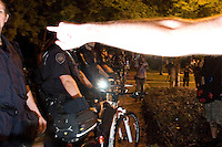 """CHARLOTTE, NC - September 3, 2012 - A marcher points at police officers. Protesters said they only wanted to march through the residential area to get back to their """"camp,"""" and some shouted angrily at police when they blocked their path."""