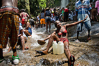 A Haitian woman performs a bathing and cleaning ritual under the waterfall during the annual religious pilgrimage in Saut d'Eau, Haiti, July 16, 2008. Every year in summer thousands of pilgrims from all over Haiti make the religious journey to the Saut d'Eau waterfall (100km north of Port-au-Prince). It is believed that 150 years ago the spirit of Virgin Mary (Our Lady of Mount Carmel) has appeared on a palm tree close to the waterfall. This place became a main pilgrimage site in Haiti since then. Haitians wearing only underwear perform a bathing and cleaning ritual under the 100-foot-high waterfall. Voodoo followers (many Haitians practise both voodoo and catholicism) hope that Erzulie Dantor, the Voodoo spirit of water, manifest itself and they get possessed for a short moment, touched by her presence.