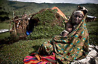 A mother and child displaced by the violence sit outside their shelter in Kilolirwe IDP site, North Kivu, DRC, on Sunday, March. 9, 2008..