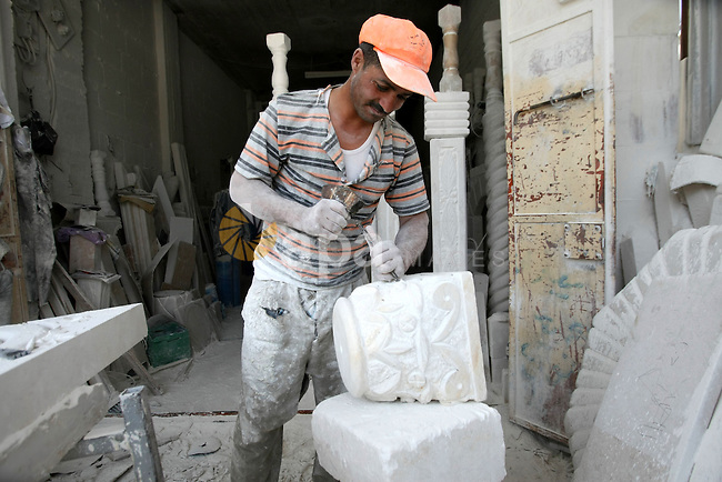 A Palestinian labourer works at a marble workshop on the eve of Labor Day, in the West Bank city of Hebron April 30, 20130. Stone and marble factories and quarries, located mainly in the West Bank cities of Bethlehem and Hebron, are at the core of the Palestinian industrial sector. According to the Union of Stone and Marble Industry, the industry employs about 16,000 administrative, skilled and unskilled labourers. Photo by Mamoun Wazwaz