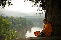 A young novice monk find solitude above the banks of the Nam Khan or Khan River in Luang Prabang, Laos.