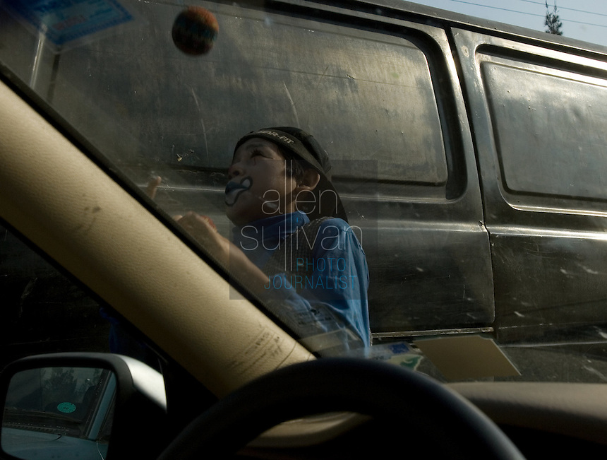 A street child, dressed as a clown, performs for money in Zone 11 in Guatemala City, Guatemala on Friday, March 9, 2007.