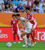 Abby Wambach (l) of Team USA and Ri Ye Gyong of Team North Korea during the FIFA Women's World Cup at the FIFA Stadium in Dresden, Germany on June 28th, 2011.