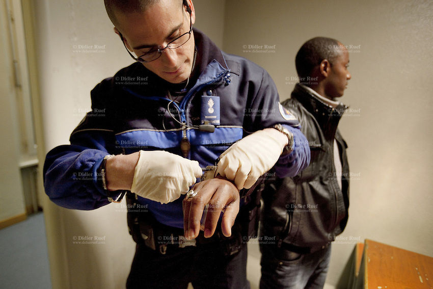 Switzerland. Geneva. Paquis police station. A pollice officer opens with a key the handcuffs of an african man from Guinea who was arrested for selling drugs in the streets. A police station or station house is a building which serves police officers and contains offices, temporary holding cells and interview/interrogation rooms. 18.03.12 © 2012 Didier Ruef