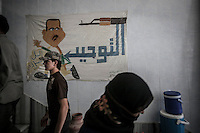 Syrian civilians pass by walk in front of a cartoon of president Bassar Al Assad at the entrance of Saraya, the main court house in downtown of Manbij City, where the head office of the top committee that rules the city is located.