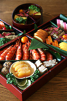 Japanese New Years food is called osechi-ryori, and consists of many different kinds of dishes.  Traditionally, people finish cooking osechi dishes by New Year's Eve so they have food for a couple days without cooking. Most of the dishes can last a few days in the refrigerator or at cool room temperature. Colorful osechi-ryori dishes are packed in layers of lacquer boxes, called jubako.  (Smaller boxes are called 'bento' which are a common sight at lunchtime throughout Japan, in schools, offices and trains.)  Each dish and type of food in osechi has meaning, such as good health, fertility, good harvest, happiness, long life, and so on.
