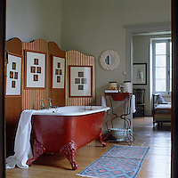 A red-oxide painted ball-and-claw bath stands in front of a red and gold striped folding screen in this ensuite bathroom