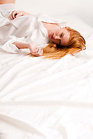 Young red haired woman laying in bed