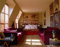 In this long attic bedroom a double bed is flanked by a pair of red velvet sofas on either side of a leopard-print rug