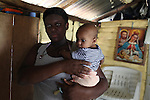 Odalisi Toribio, 19, from La Cerca, holds her three-month old daughter Marisol. Barrick and Goldcorp's Pueblo Viejo open-pit gold mine threatens the cocoa-bean producing community of La Cerca. Cotuí, Sánchez Ramírez, Dominican Republic. April 2012.