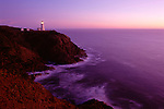 Northhead Ilwaco lighthouse at sunset along the Washington coastline Pacific ocean with rocks and cliff near Ilwaco Washington State USA