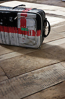 A standard suitcase has been painted with an abstract flag