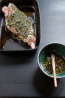 Prior to cooking a leg of lamb is marinaded in oil and herbs