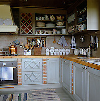 The woodwork in this kitchen is painted pale grey and the drawers are decorated with criss-cross moulding