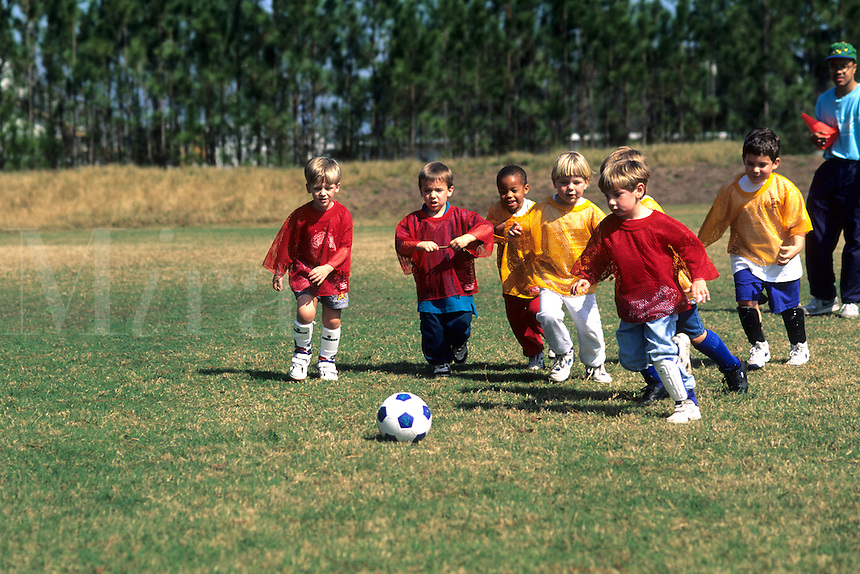 Young boys age 5 thru 7 playing organized soccer football on a team together