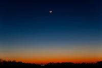 Extremely sunset with crescent Moon on a late winter day in the North Texas area. Scene photographed in a rural area near the city of Palmer, Texas. Comet Pan-STAAR is barely visible between the Moon and the horizon.