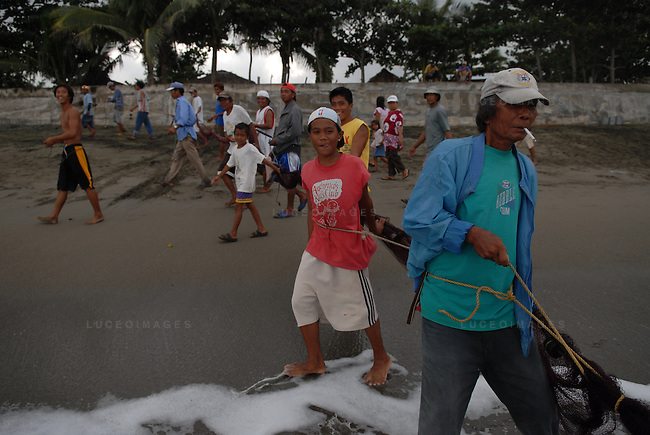 Villagers help to pull in a massive fishing net in order to take their share of the catch in Ilocos Norte, Philippines..**For more information contact Kevin German at kevin@kevingerman.com