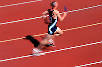 Blurred action image of a male runner at a track meet.