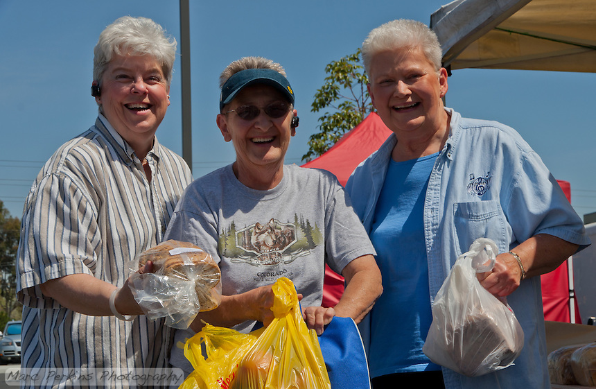 Mandi, Willie, and Sue at South Coast Collection's Farmers' Market happily displaying their purchases.  SR.
