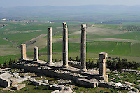 Oblique view of a row of columns from the Temple of Saturn, built around 200 A.D., with the landscape in the background, in Dougga, Tunisia, pictured on January 31, 2008, in the morning. Dougga has been occupied since the 2nd Millennium BC, well before the Phoenicians arrived in Tunisia. It was ruled by Carthage from the 4th century BC, then by Numidians, who called it Thugga and finally taken over by the Romans in the 2nd century. Situated in the north of Tunisia, the site became a UNESCO World Heritage Site in 1997. This temple was previously the site of the Punic Temple of Baal. The entrance had four Corinthian columns which remains are still visible. Picture by Manuel Cohen.