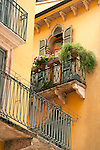 A balcony with pink flowers, a window with shudders, and an iron railing of a yellow house in Verona, Italy.