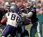Oakland Raiders vs. San Diego Chargers at Oakland Alameda County Coliseum Sunday, October 11, 1998.  Raiders beat Chargers  7-6.  Oakland Raiders defensive back Anthony Newman (30) stops San Diego Chargers running back Natrone Means (20).