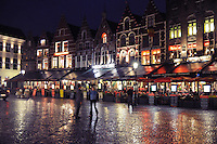 Rainy night in Bruges (Brugge). City square with neon lights reflections on the brick streets.