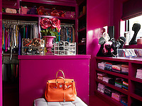 A vibrant dressing room features walls and custom-made cabinetry painted in Dulux's Russian Velvet 3 a striking magenta pink.