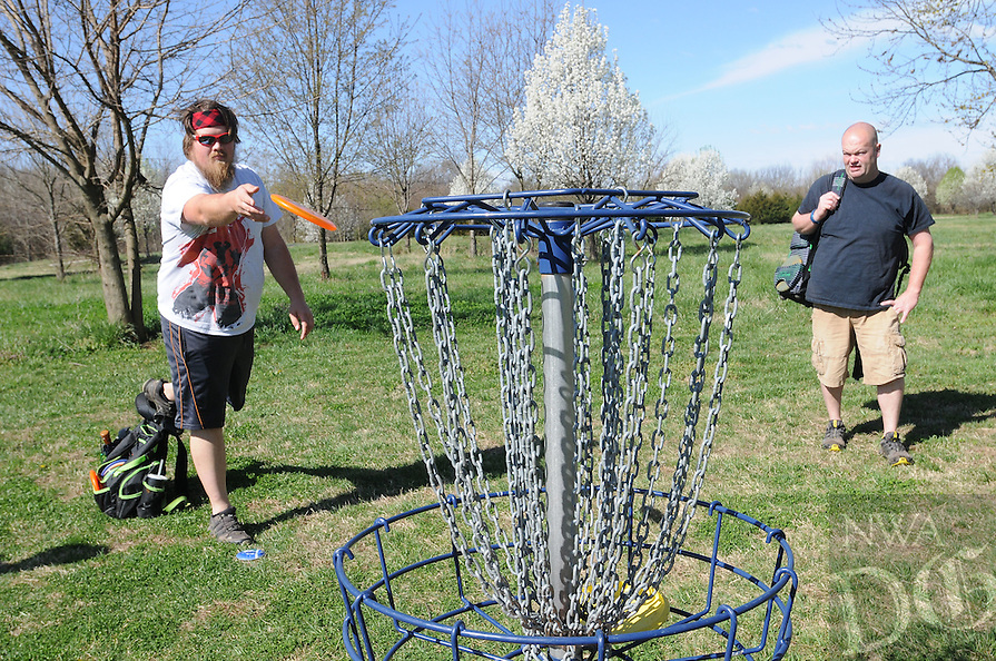 NWA Democrat-Gazette/FLIP PUTTHOFF <br /> SHORT PUTT<br /> Nathan Weeks (left) makes a toss into the basket during a game of disk golf Wednesday March 16, 2016 while Brandon Reynolds watches the shot. The two, along with Josiah Mason, all of Siloam Springs, played the game at the disk golf course at the Blossom Way trail access next to Rogers High School on Dixieland Road. Disk golf is scored similar to regular golf and is just as fun, the guys said. Various disks function as drivers, irons and putters.