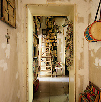 The hallway has a rustic feel, with a distressed finish on the walls and a flagstone floor. A view through an open doorway leads to a room lined with bookshelves