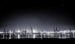 A black and white night photograph of the Nile passing in front of Luxor Temple and town.