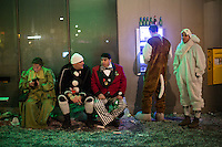 On the final night of festivities, less than two hours before the end of Fasnacht, the Carnival of Basel, costumed participants sit on a bench as others stand next to an ATM. Basel, Switzerland. Feb. 26, 2015.