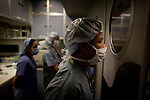 Dr. Ninh Duc Nguyen watches Dr. Steve Charles, of Memphis, perform a retina reattachment surgery on board the ORBIS Flying Eye Hospital on Wednesday, April 15, 2008. The operating room is only big enough for two additional observing doctors during surgery.  All operations are broadcasted in a theater at the front of the plane for additional doctors to watch. Kevin German /  kevin@kevingerman.com..ORBIS Flying Eye Hospital brought doctors, nurses and specialists from all over the world to Ho Chi Minh City, Vietnam from April 7-18, 2008.  The ORBIS program contributed to the efforts of Ho Chi Minh City Eye Hospital in fighting avoidable blindness by educating local ophthalmologists to diagnose and manage pediatric blindness, retinal disease, oculoplastics, and blindness due to glaucoma..