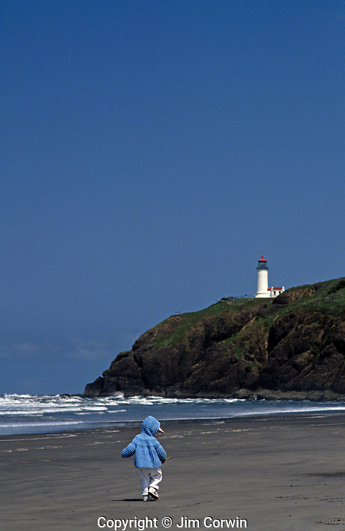 Child walking along ocean beach with Northhead lighthouse