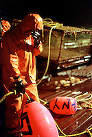 """After working for 24 hours straight, a crewman onboard the fishing vessel """"Maverick"""" rests his eyes as he awaits the signal to throw the buoy and dump the crab pot overboard during King Crab crab fishing season in the Bering Sea in November 1993.  The Bering Sea is known for having the worst storms in the world.  Nights are long and cold in the arctic in the winter.  Crab fishing in the Bering Sea is considered to be one of the most dangerous jobs in the world.  This fishery is managed by the Alaska Department of Fish and Game and is a sustainable fishery.  The Discovery Channel produced a TV series called """"The Deadliest Catch"""" which popularized this fishery."""
