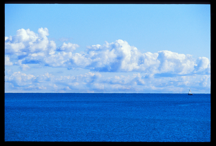 A LONE SAILBOAT IS DWARFED BY A BRIGHT BLUE LAKE SUPERIOR AS IT CRUISES THE WATERS OFF MARQUETTE MICHIGAN UNDER PUFFY CLOUDS.
