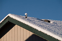 Fresh snow on a house rooftop in Monroe, Washington, USA following a winter snow storm in the Pacific Northwest.
