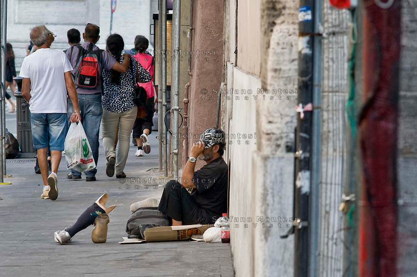Roma 10 Agosto 2014<br /> Un uomo chiede l'elemosina , mostrando la gamba artificale, in Corso del Rinascimento. <br /> Rome August 10, 2014 <br /> A man begs for alms, showing the artificial leg, in course of the Renaissance.